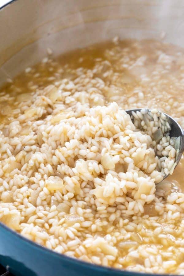 stirring rice in a pot