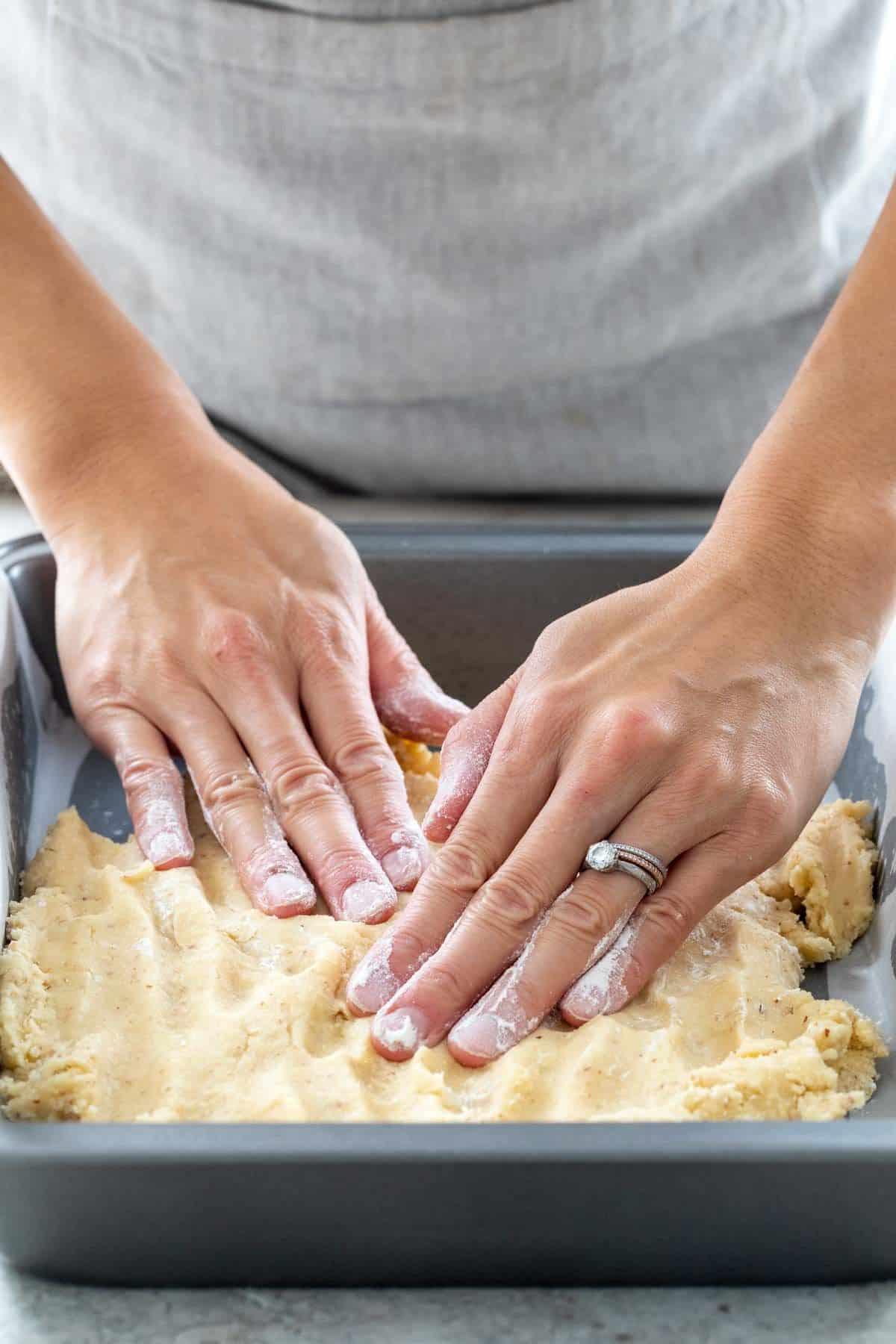 person spreading dough into a baking dish