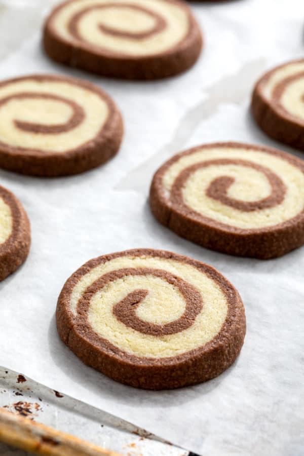 pinwheel cookies baking on a sheet tray