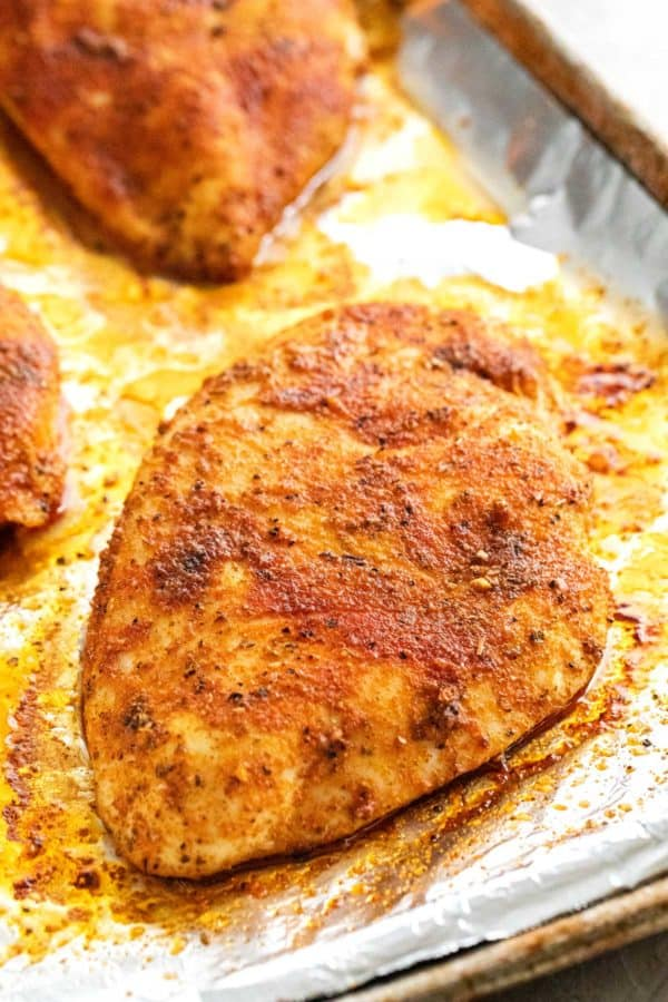 Close up of a golden browned chicken on aluminum foil