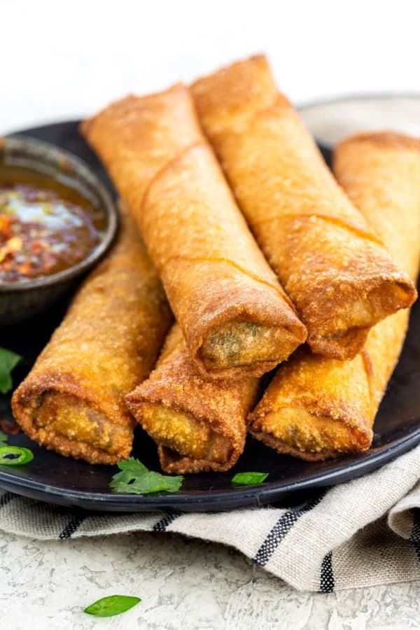 serving platter with egg rolls and a dipping sauce