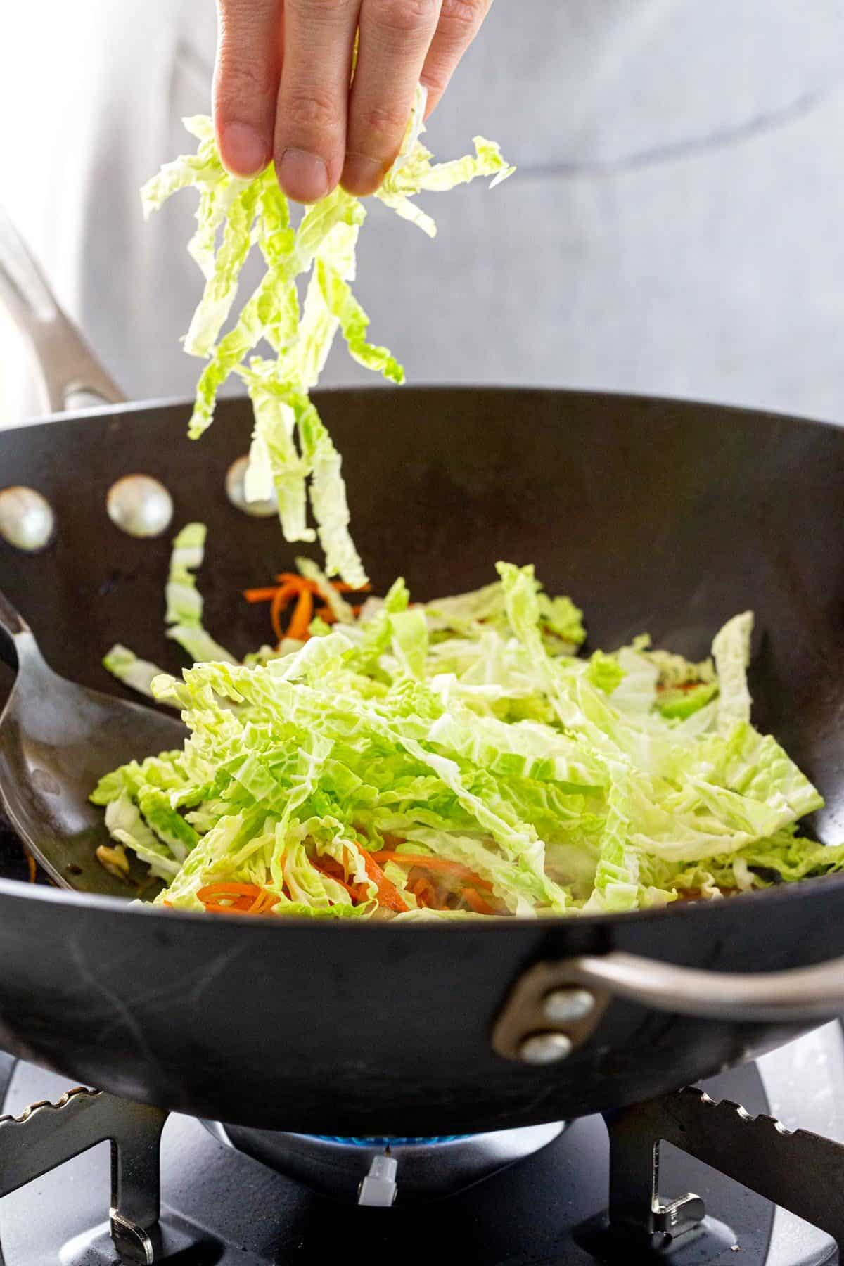 adding shredded cabbage to the pot