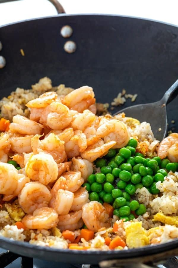 shrimp and peas being added to a wok