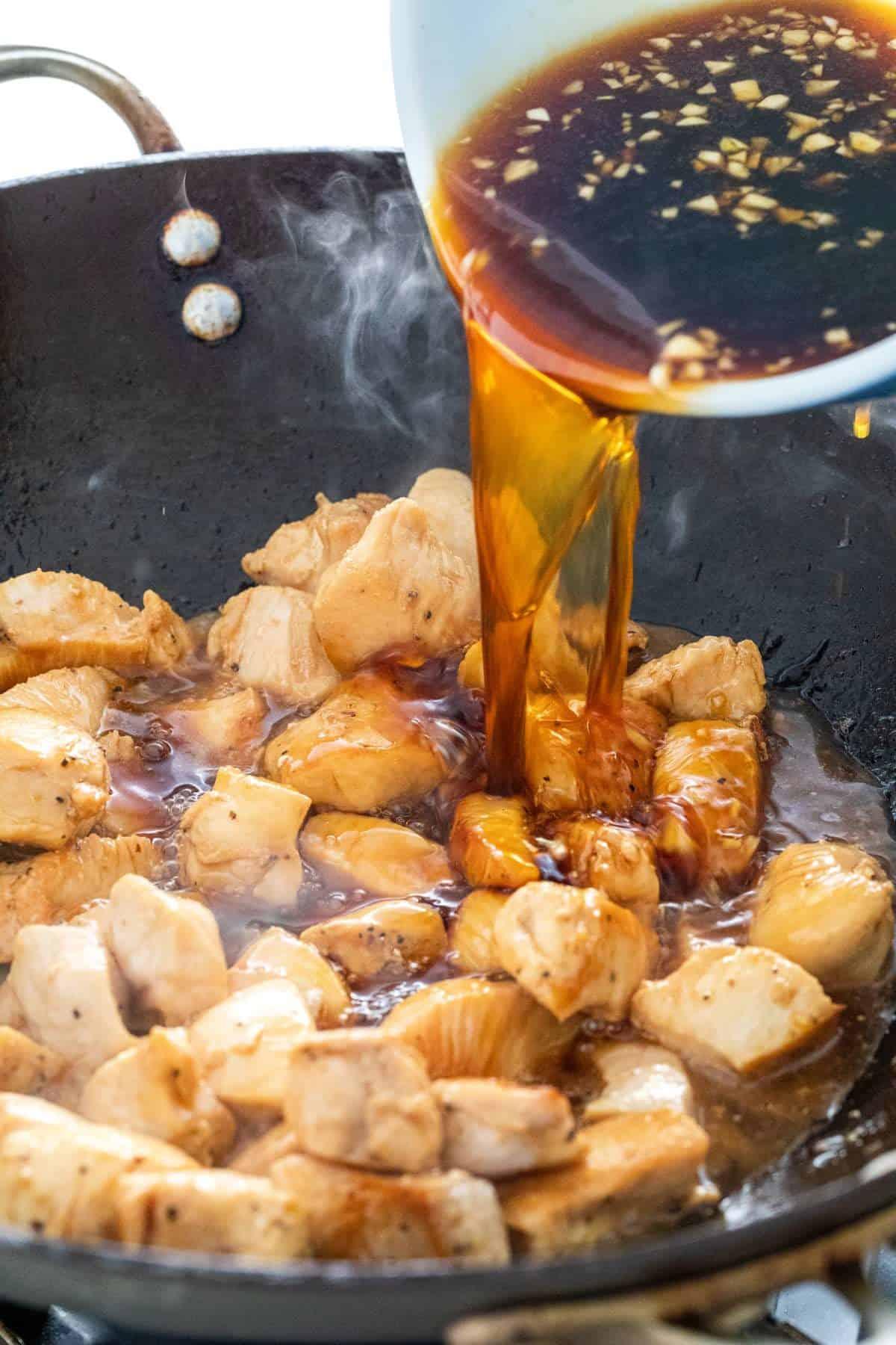 adding the teriyaki sauce to the pan of chicken