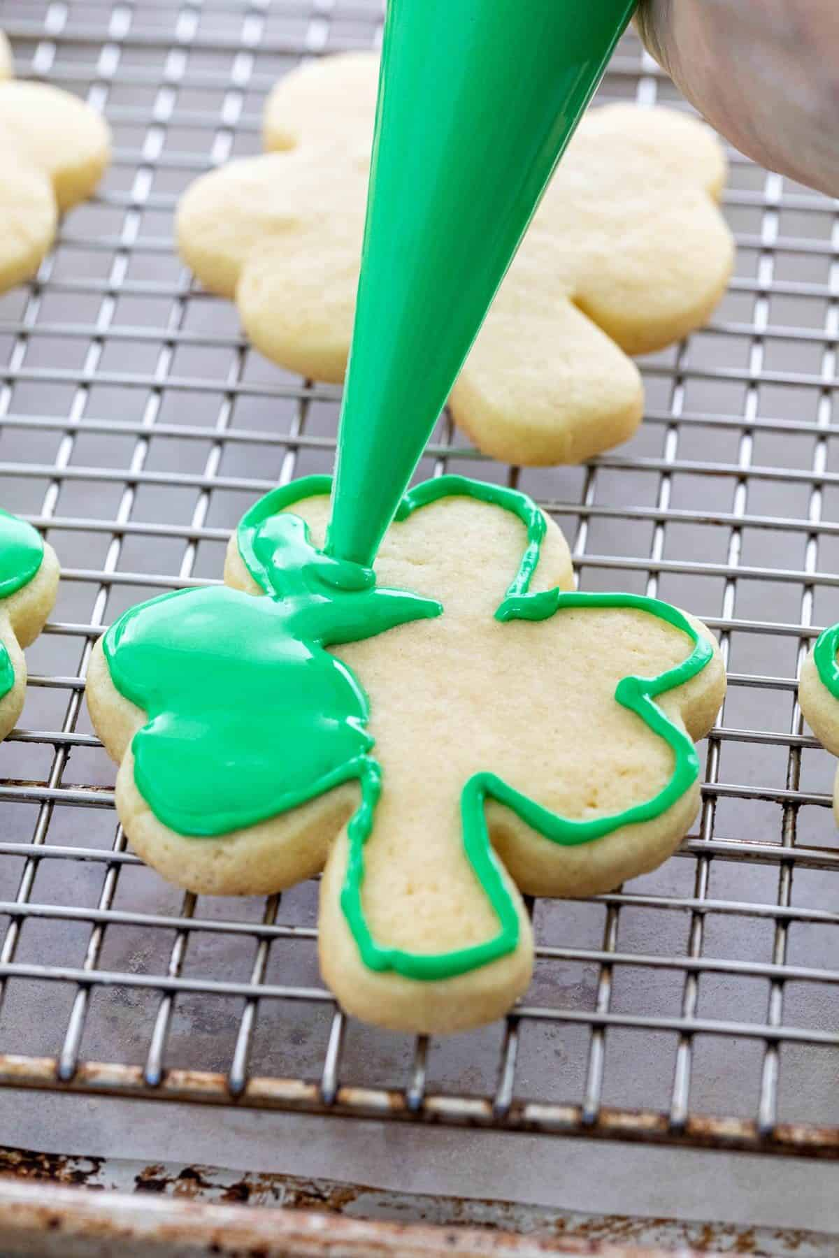 piping flood icing on a shamrock cookie