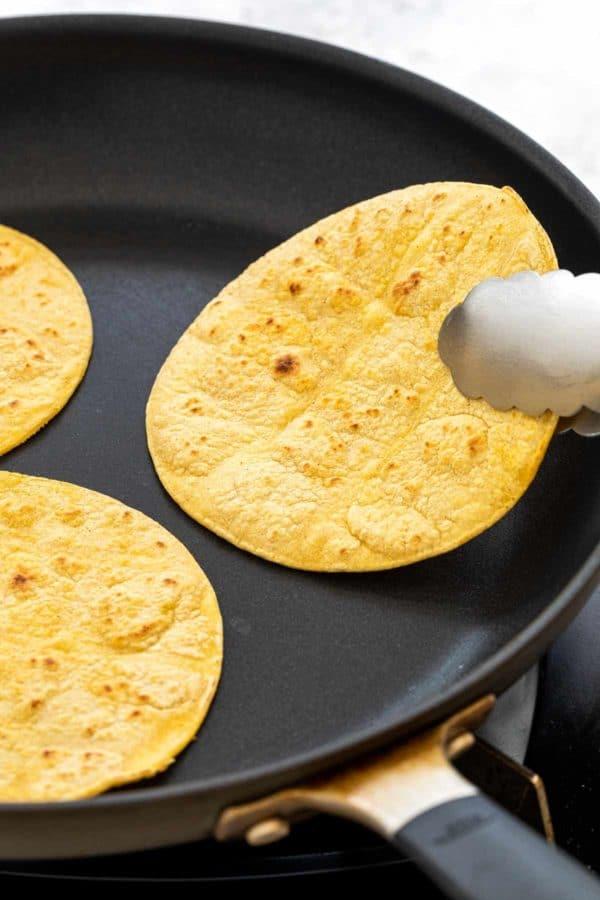 warming corn tortillas in a pan