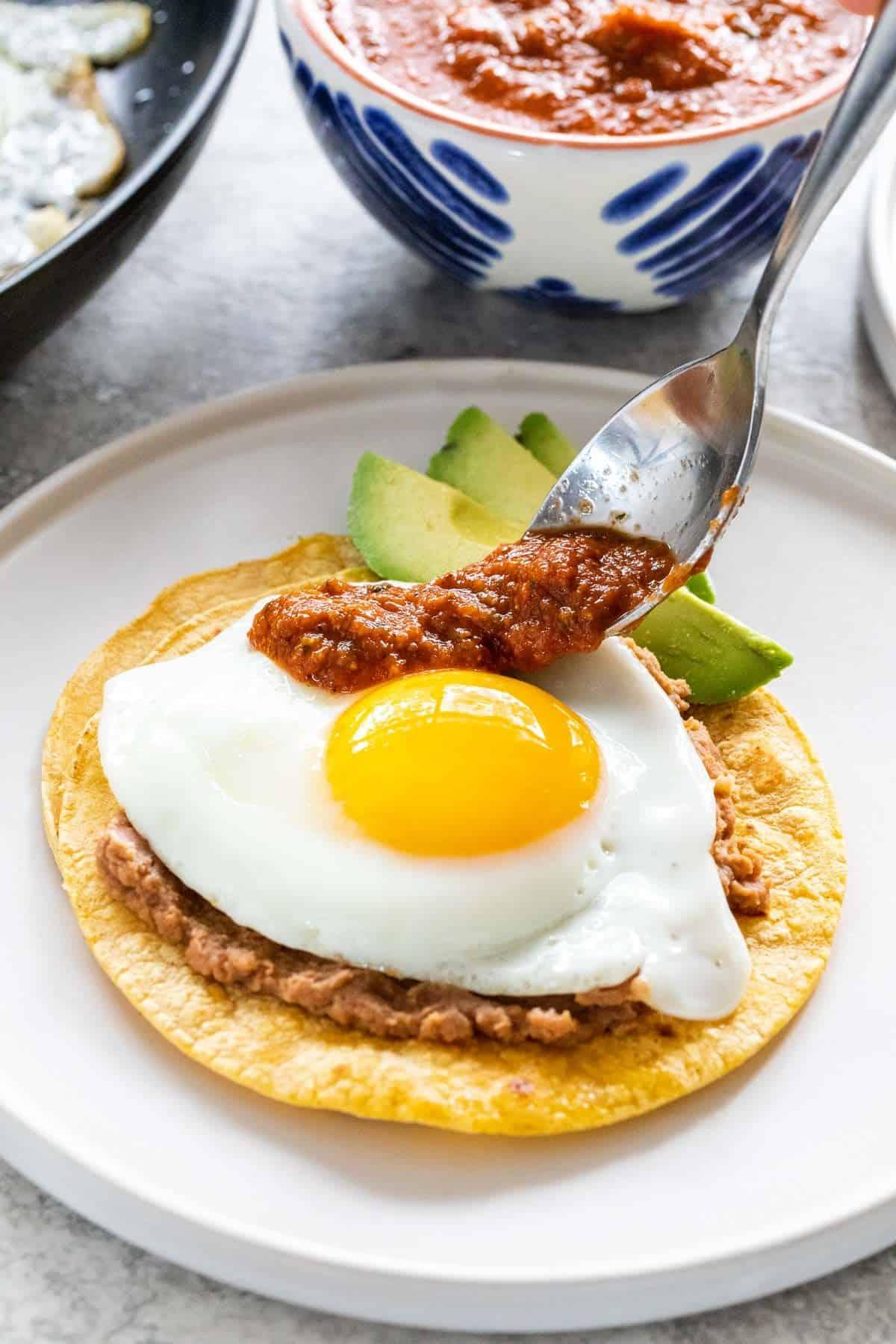 spooning ranchero sauce on the egg
