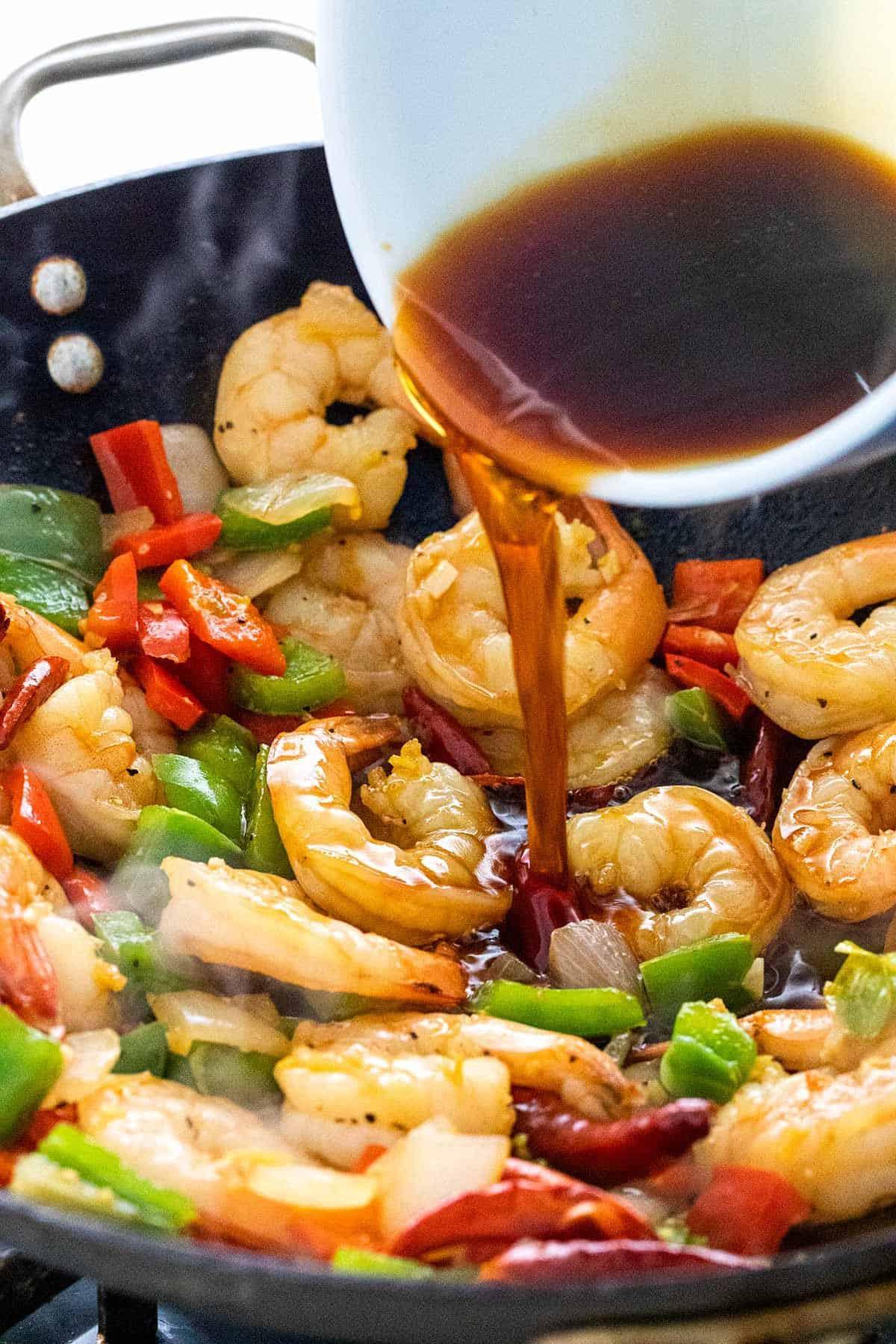 adding stir fry sauce to the pan