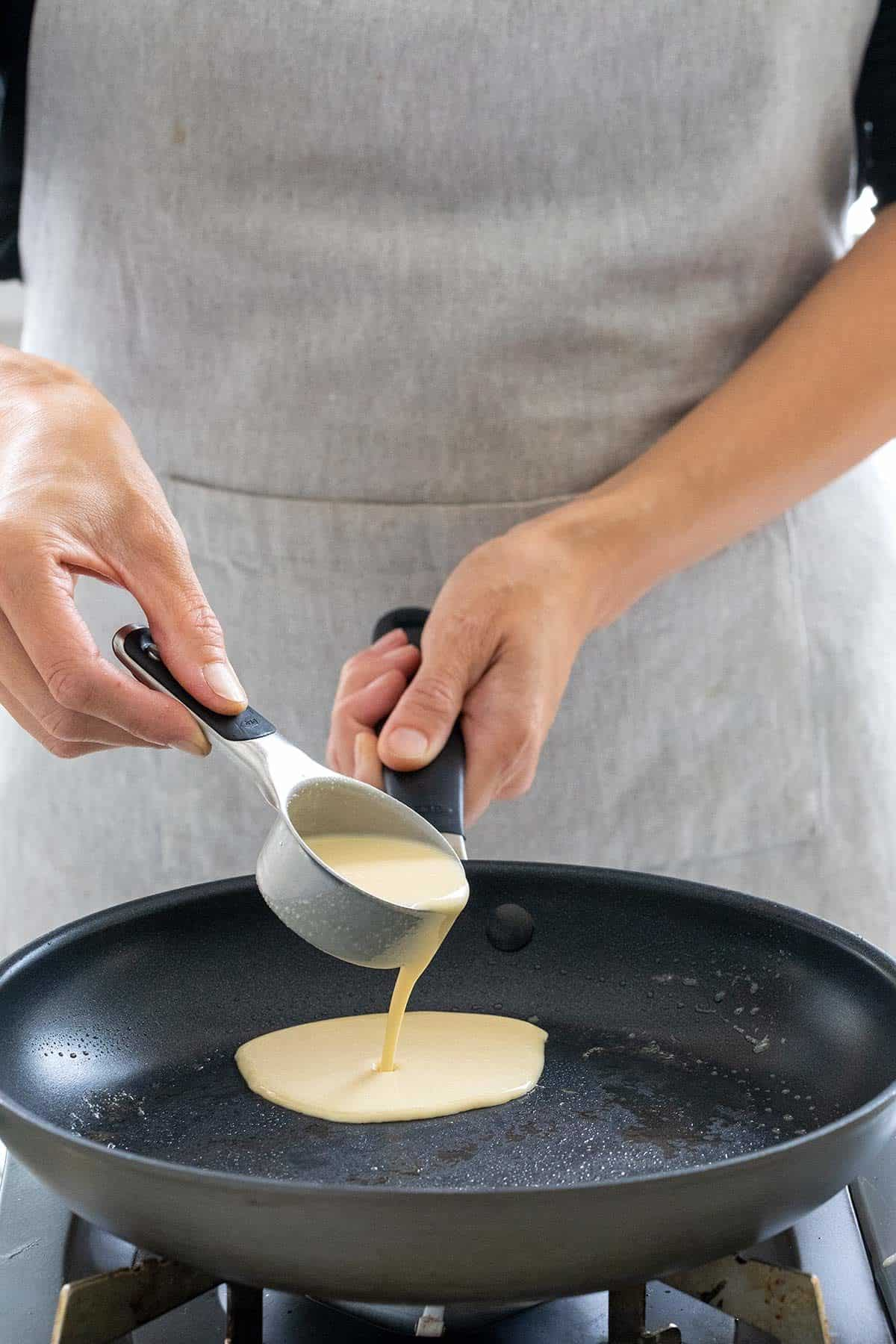 pouring crepe batter into a nonstick pan