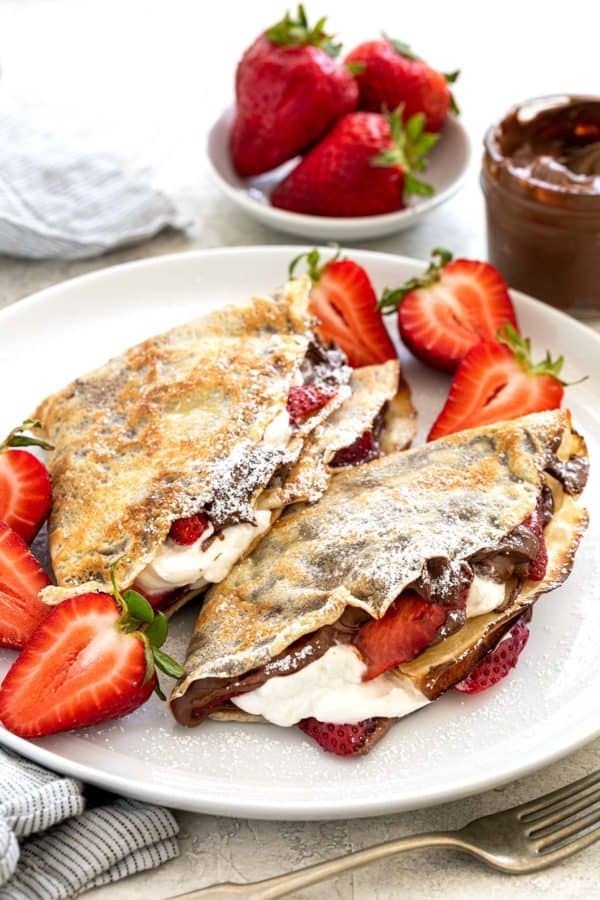 nutella crepes on a plate with sliced strawberries