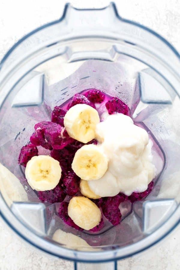 banana, yogurt and fruit in a blender cap