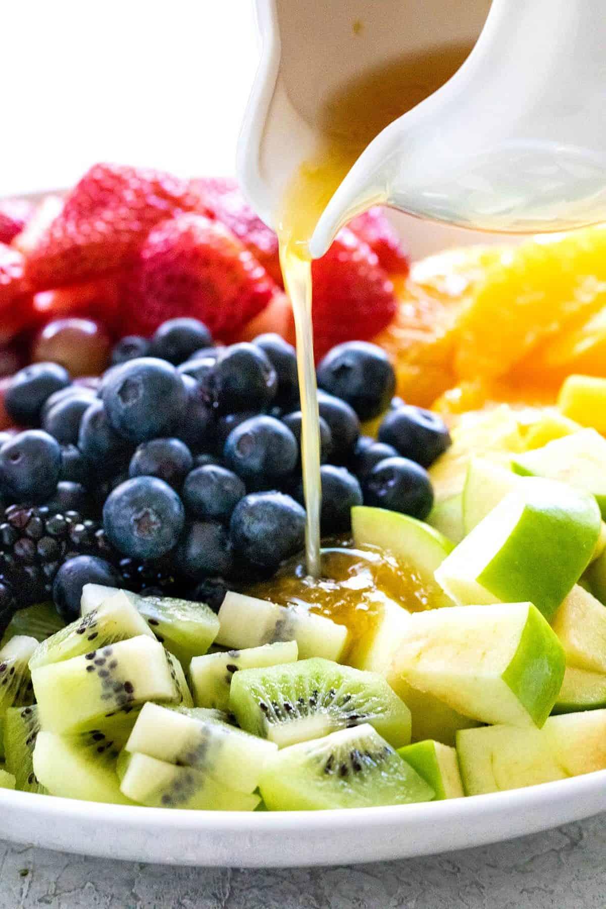 pouring salad dressing over fruit