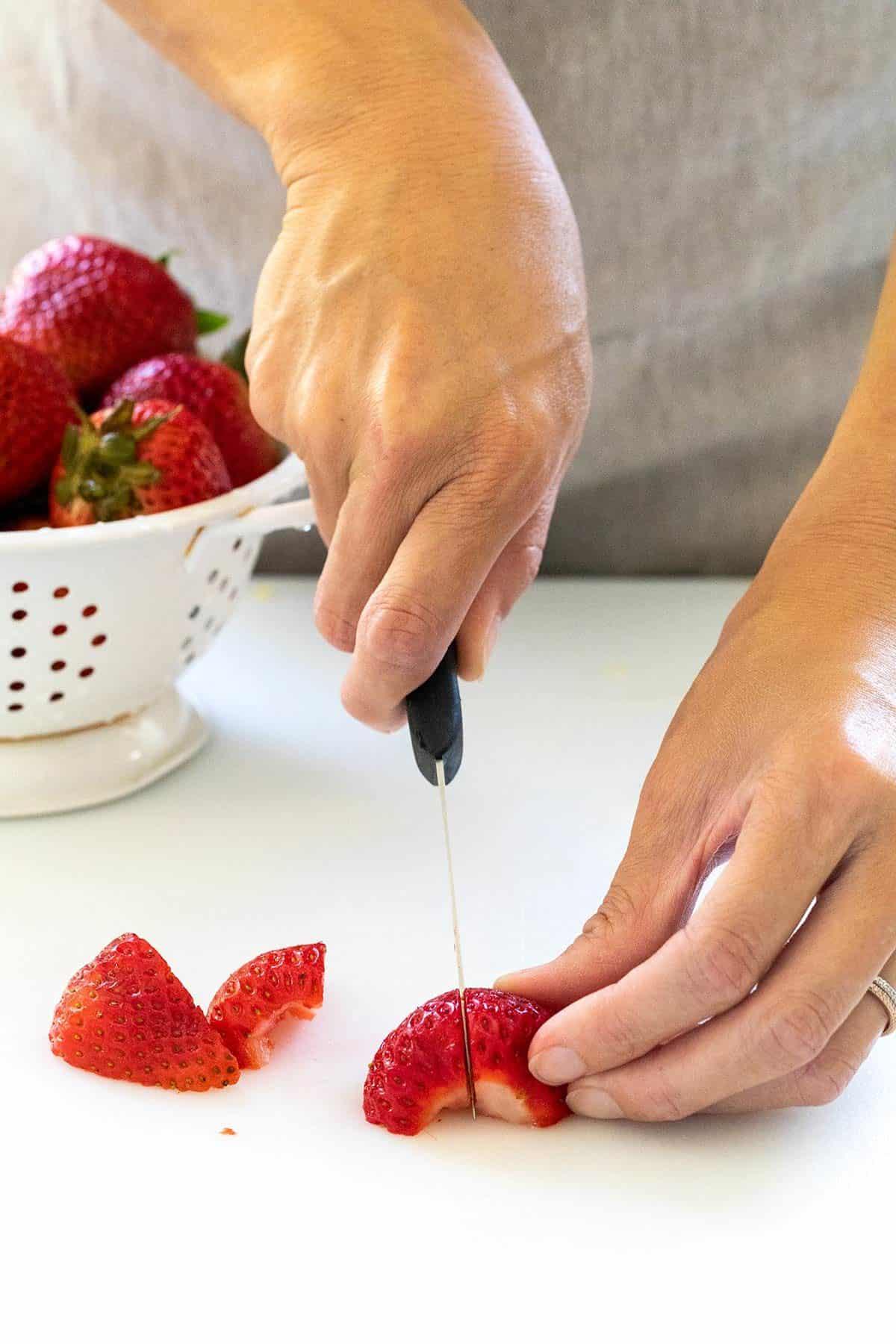 cutting strawberries in quarters