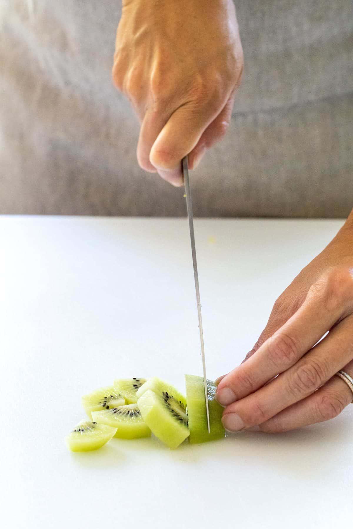 slicing kiwi on a cutting board