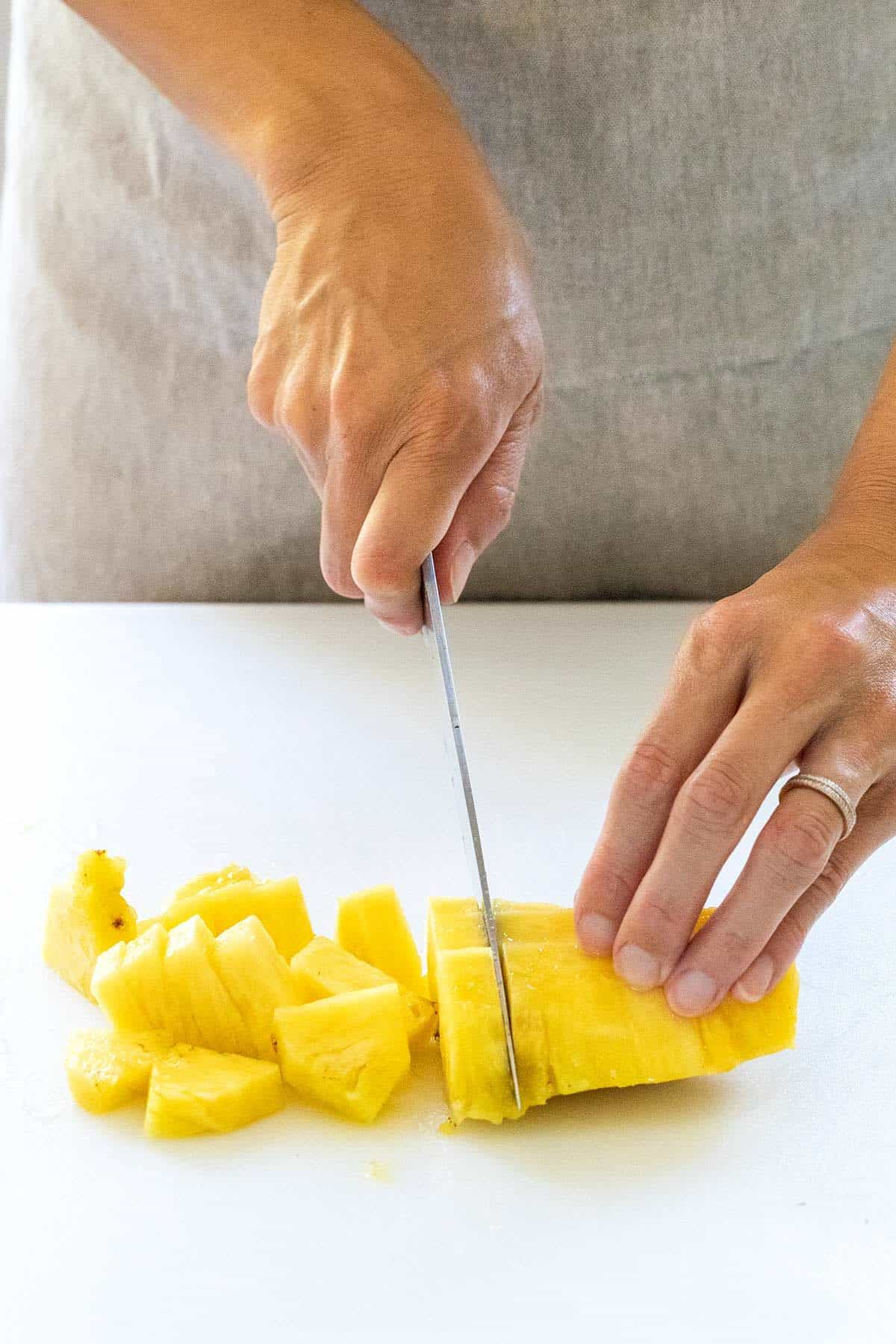cutting pineapple into smaller slices