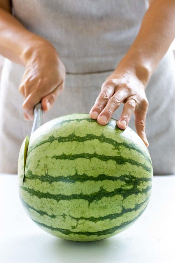 cutting one end off of a watermelon