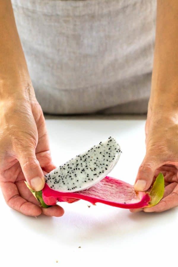 hands peeling the dragon fruit flesh off the skin