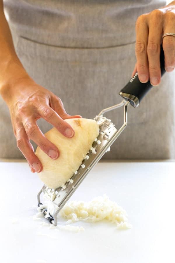 grating a piece of jicama