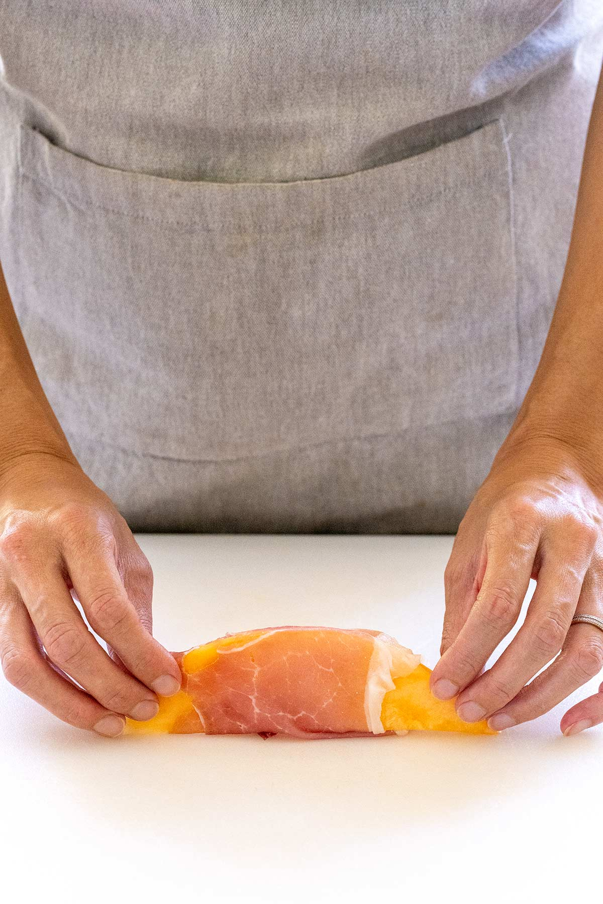 wrapping thinly sliced ham around a cantaloupe wedge