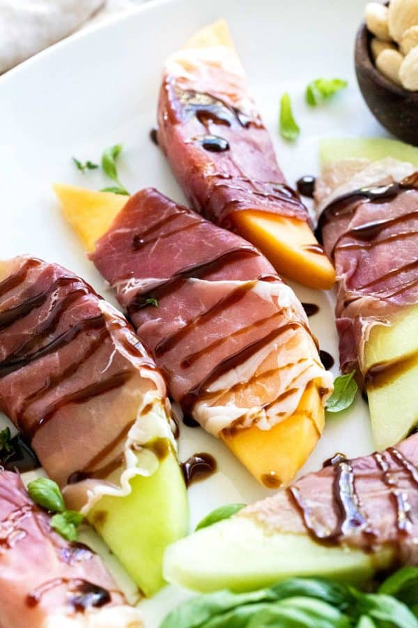 tray of cantaloupe wrapped in prosciutto