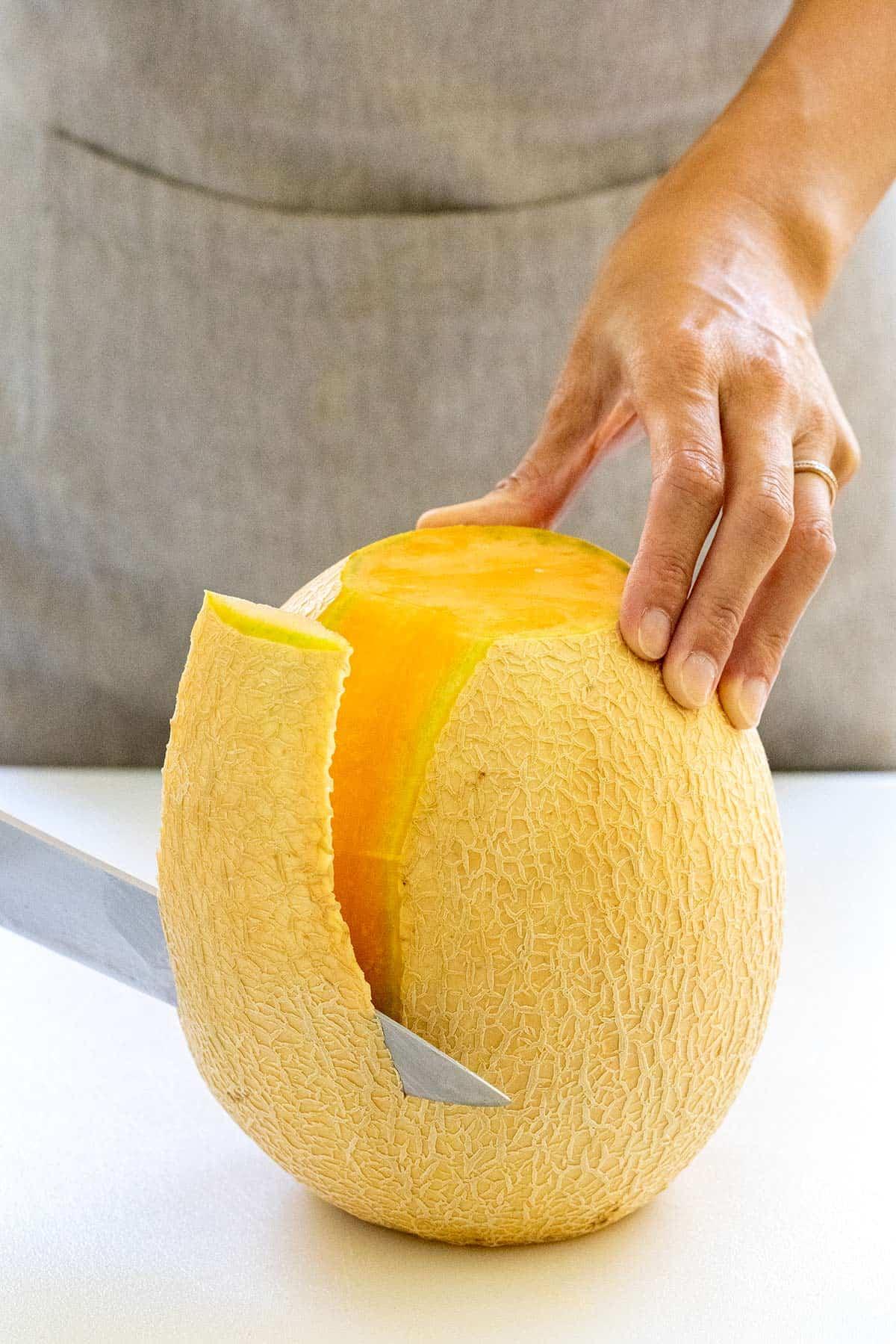 knife cutting rind off a cantaloupe