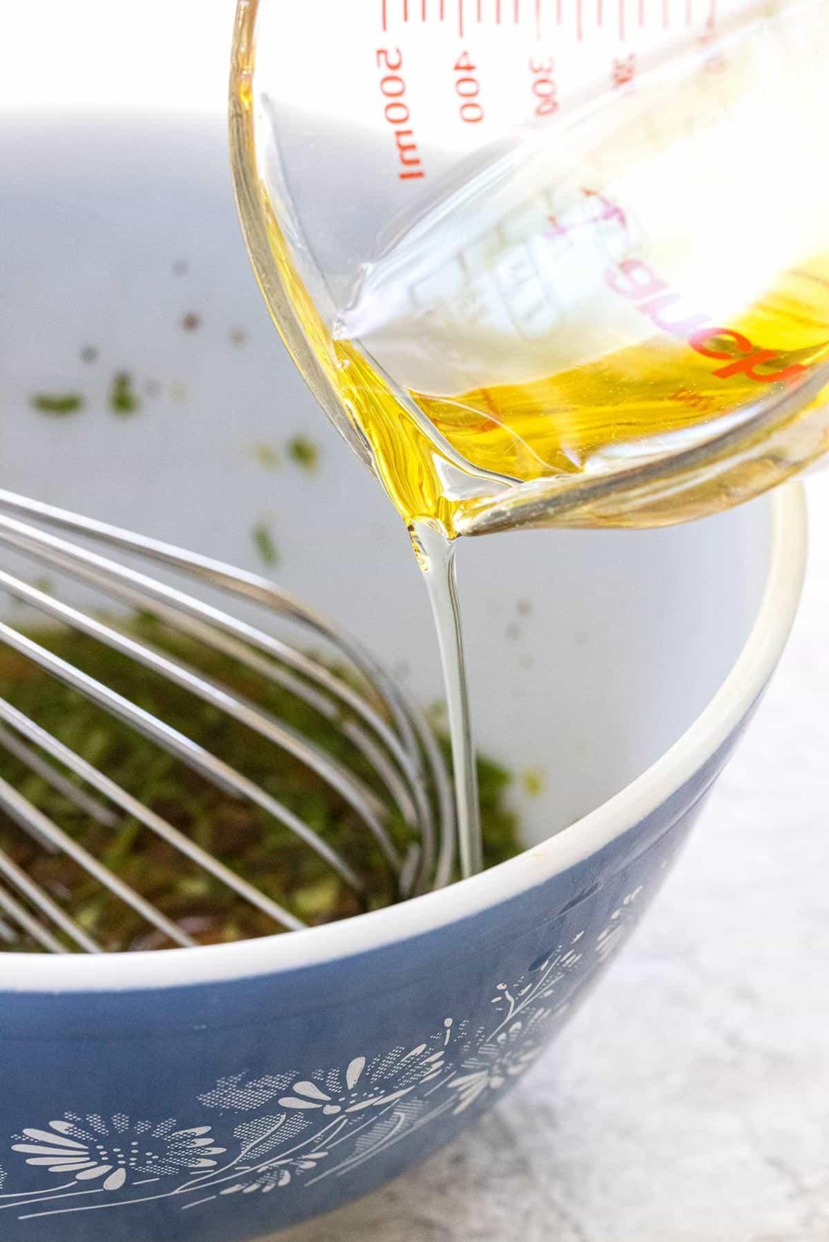 pouring avocado oil into a bowl of salad dressing
