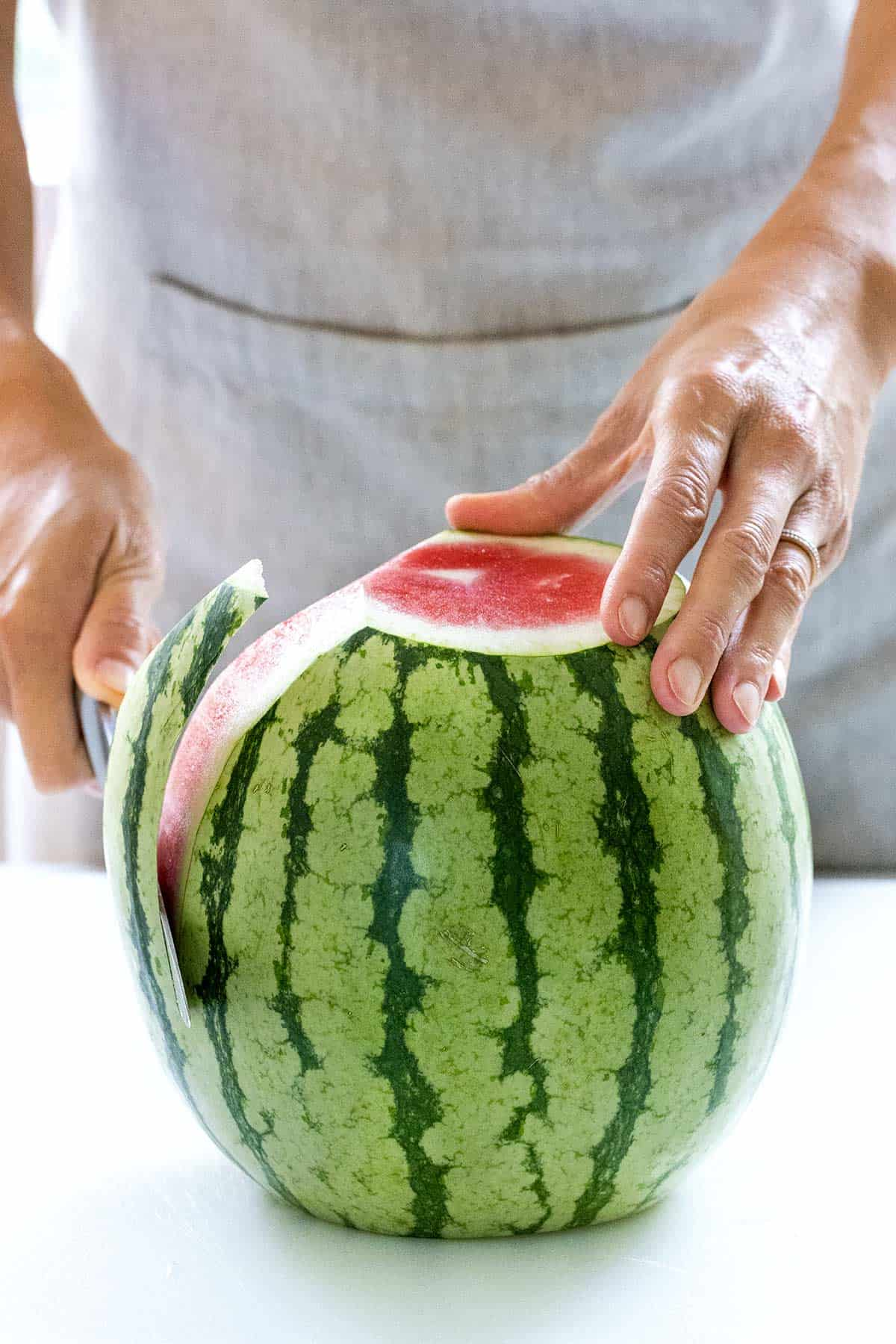 cutting the rind off a watermelon