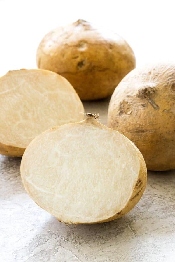 jicama sliced open showing the white flesh inside