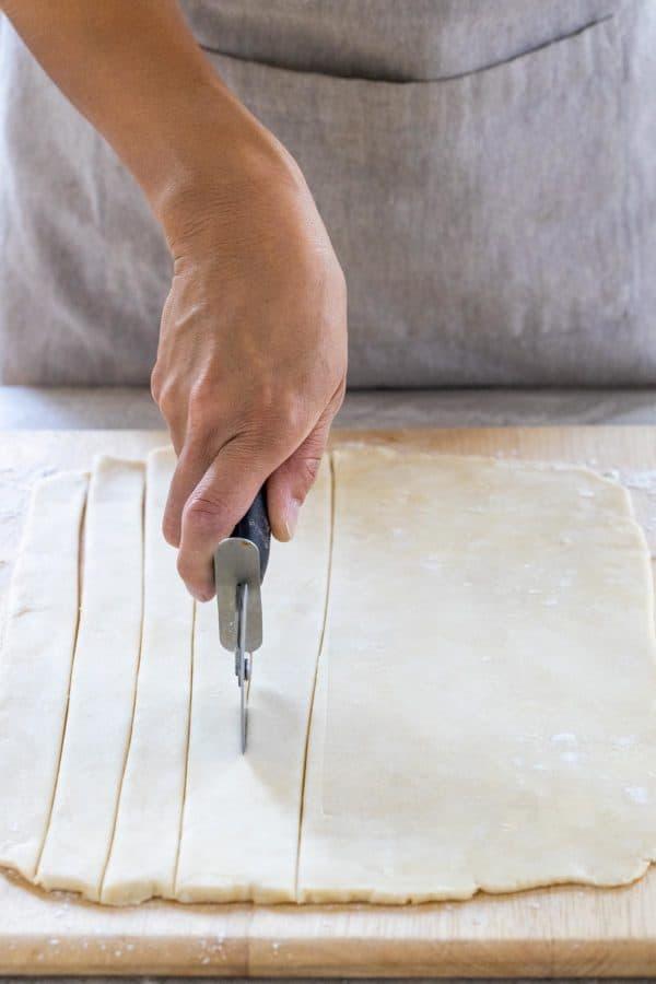 cutting flattened dough into strips