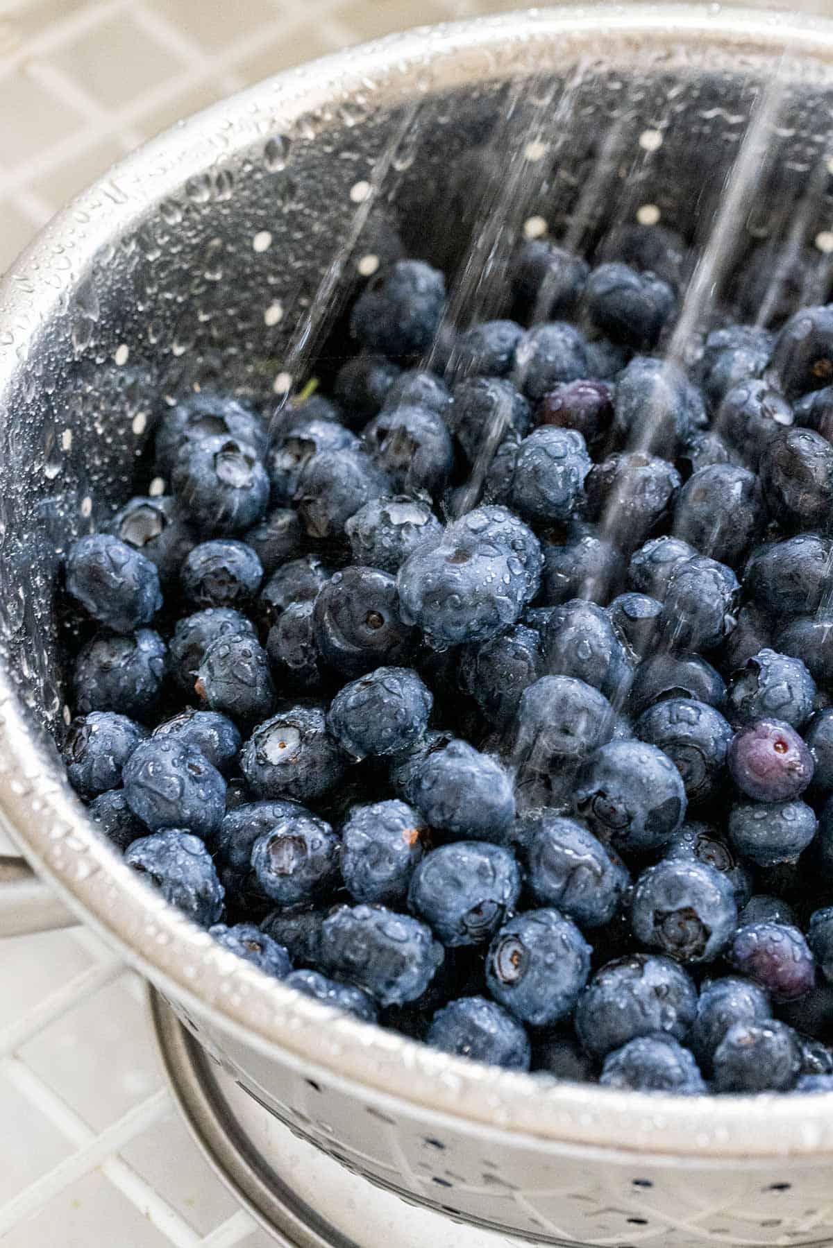 washing blueberries in a colander