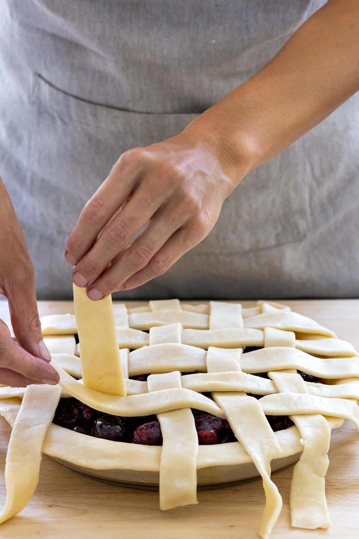 weaving dough to make a lattice crust