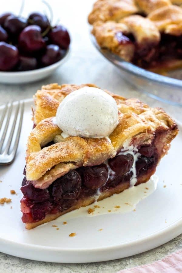 slice of cherry pie with a scoop of ice cream on top