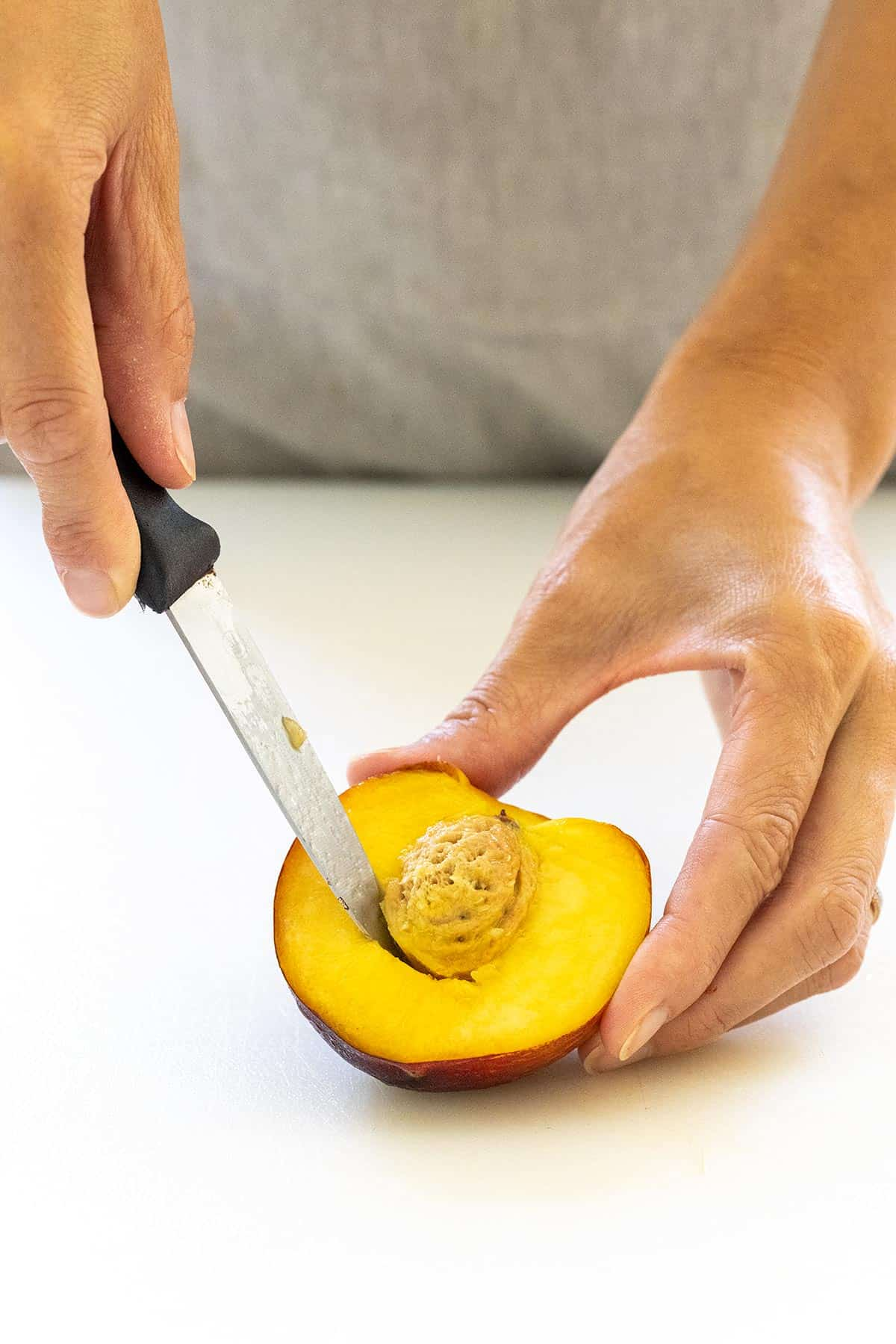 cutting a peach pit out with a knife