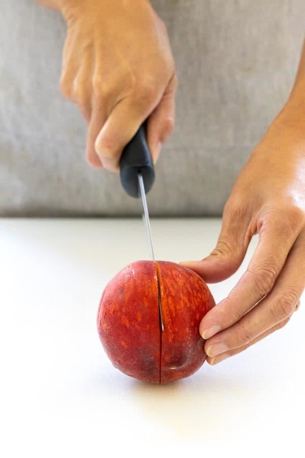 slicing a peach in half