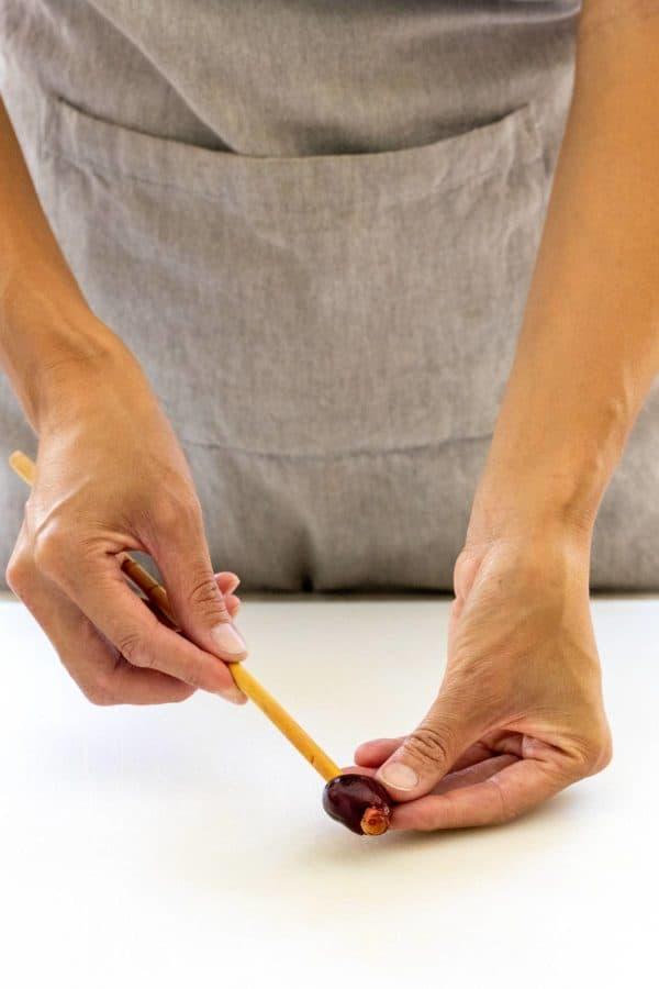 pushing a chopstick through a cherry