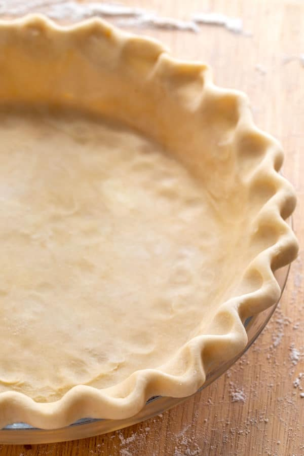 raw pie crust dough with crimped edges