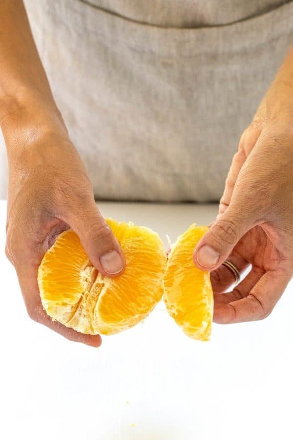 pulling apart an orange into segments
