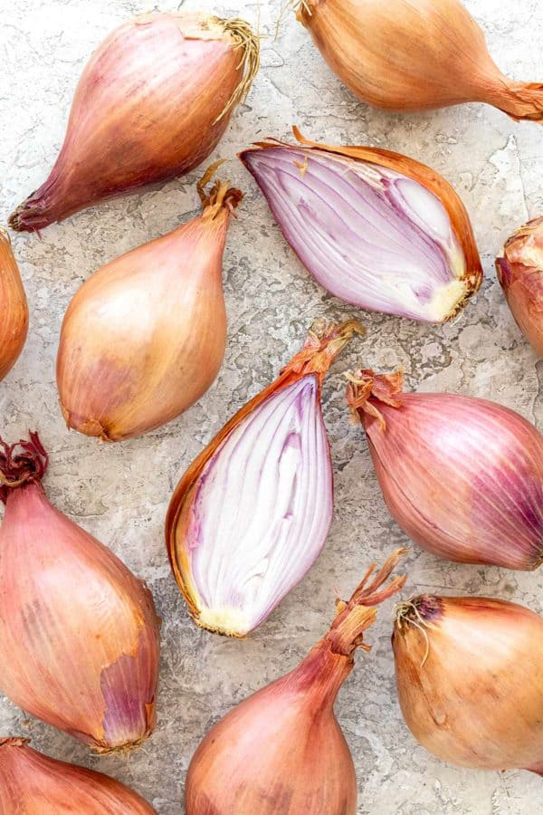 shallots on a table with one cut in half