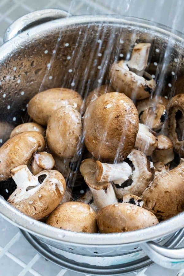 Rinsing brown mushrooms in a colander